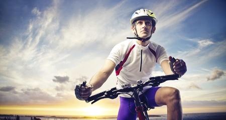 ciclista: Hombre ciclista en una puesta de sol Foto de archivo
