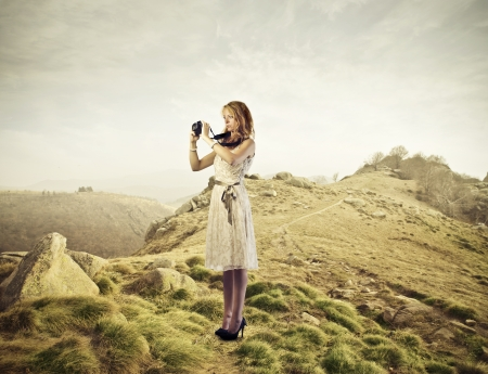 Blonde woman on a hill taking a picture photo