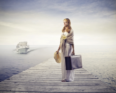 Woman waiting for a boat on a wharf photo