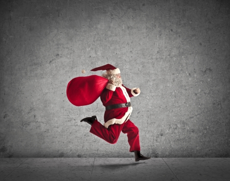 Santa Claus running with the bag of the presents photo