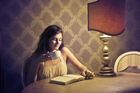 poezie: Een bruine meisje nippen van een kopje thee terwijl het is het lezen van een boek in een elegante locatie
