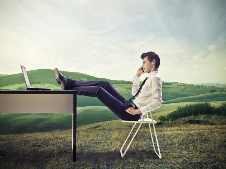 office shoes: Young businessman, on a hill, make a call with feet on desk