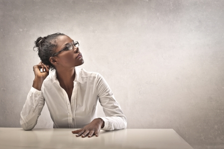 african girls: Black girl, leaning on a white desk, thinking