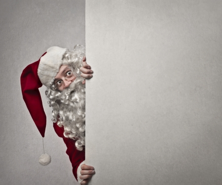 appearing: Santa Claus appearing from behind a white wall