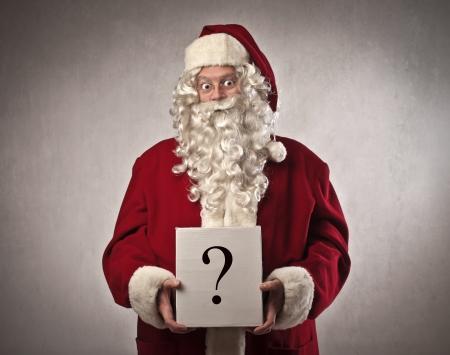 stupor: Pap� Noel con el cart�n en la que se dibuja un signo de interrogaci�n Foto de archivo