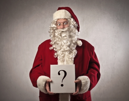 stupor: Santa Claus with cardboard on which is drawn a question mark Stock Photo