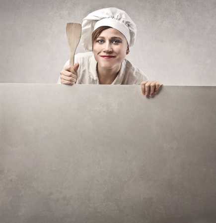 Woman cook with a wooden spoon Stock Photo