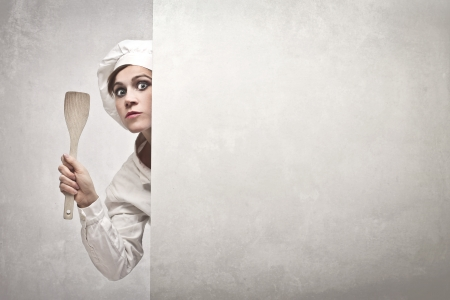 ingedient: Woman cook with a wooden spoon behind a white wall