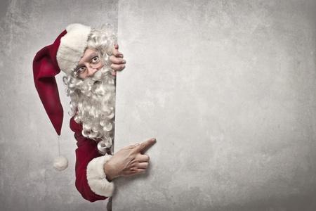 weihnachtsmann: Santa Claus zeigt etwas auf einer wei�en Wand