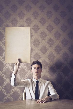 elegante: Jeune homme en cravate élever un carton blanc Banque d'images