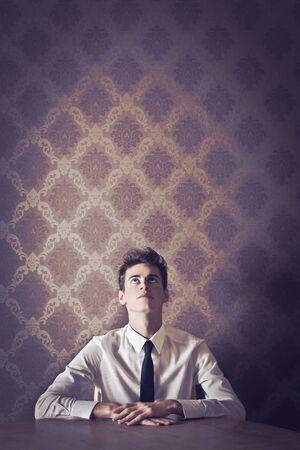 elegante: Jeune homme en cravate, en s'appuyant sur une table, regardant vers le haut