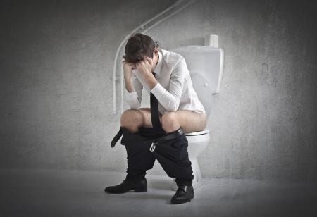 defecate: Stressato giovane uomo d'affari su un wc con le mani nei capelli Archivio Fotografico