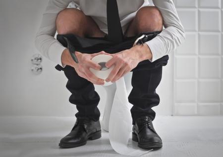 defecate: Giovane uomo d'affari sul water in possesso di un rotolo di carta igienica