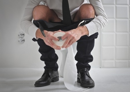 defecate: Young businessman on the toilet holding a roll of toilet paper