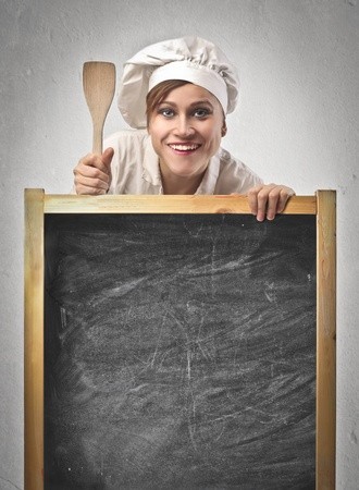Woman cook over a blackboard with a wooden spoon photo
