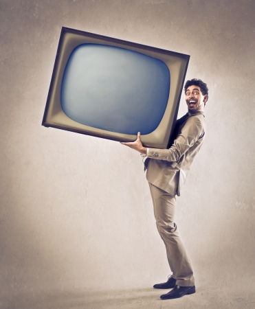 persuade: Young businessman holding a big television