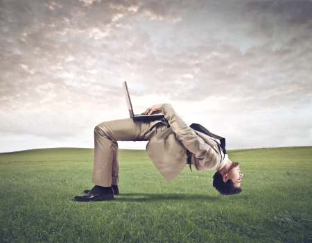 odd jobs: Young businessman using a laptop computer upside down on a large lawn