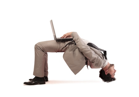 Young businessman using a laptop computer upside down photo
