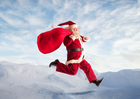 fast delivery: Santa Claus running in a mountain landscape with his sack full of presents