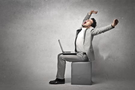 Joven hombre de negocios, sentado con un ordenador portátil, se extiende Foto de archivo