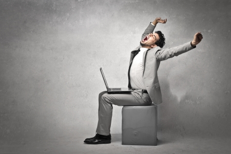 tired man: Young businessman, sitting with a laptop computer, stretches