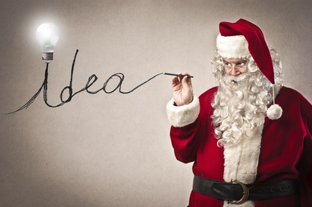 christmas costume: Santa Claus writing the word  idea  with a bulb on the initial Stock Photo