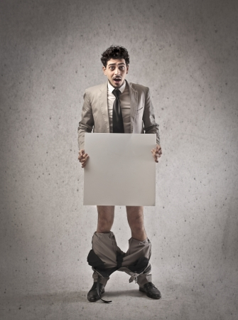 awkwardness: Young businessman covering his private parts with a white cardboard