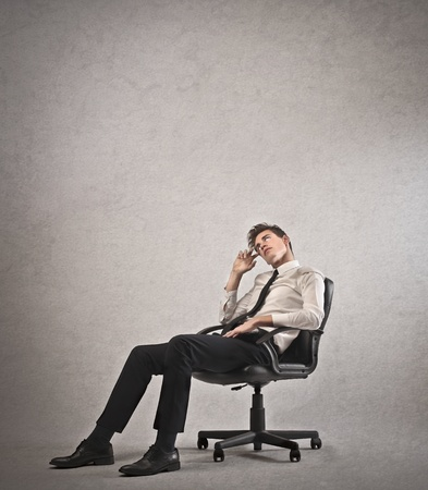 man in chair: Stressed young office worker on an office chair Stock Photo