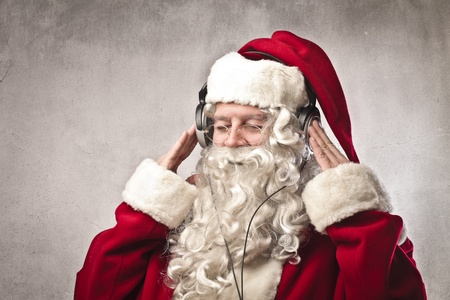 earphone: Santa Claus listening to the music with a pair of headphones Stock Photo
