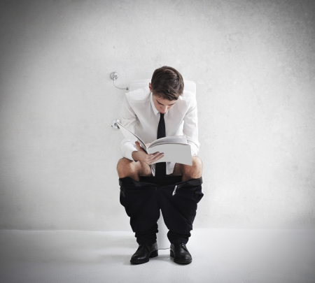 Young businessman reading a magazine on the toilet Stock Photo - 16621352