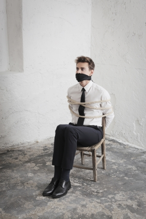 gagged: Young businessman tied to a chair and gagged in a basement Stock Photo