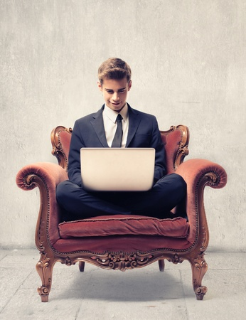 Young businessman, sitting on an vintage armchair, using a laptop computer photo