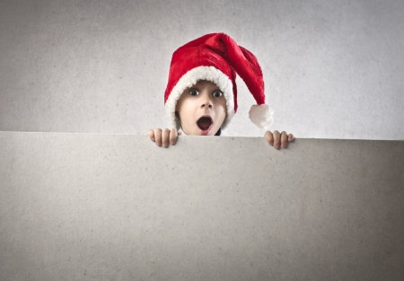 Amazed baby with a christmas hat over a white cardboard Stock Photo - 16621355