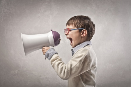 announce: child screaming with megaphone on a gray background Stock Photo