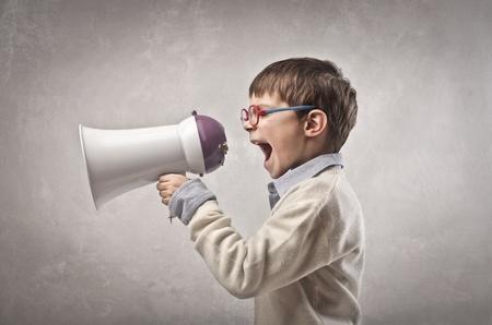 hombre megafono: ni�o gritando con el meg�fono en un fondo gris