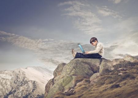 child sitting on the rocks writes with laptop photo