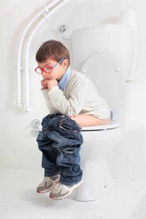 defecate: bambino che si siede sul water