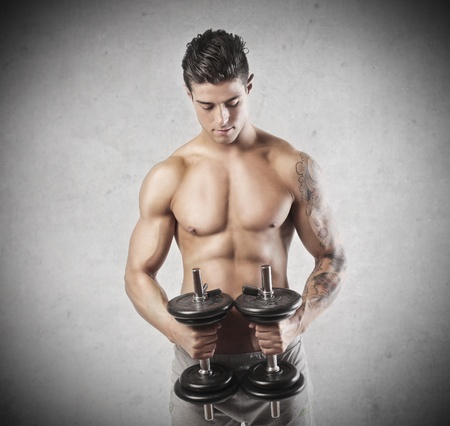 handsome muscular guy does physical exercises with weights Stock Photo - 17230542