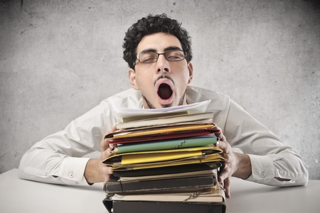 worker sleepy yawn with face resting on pile of books Stock Photo - 17237246