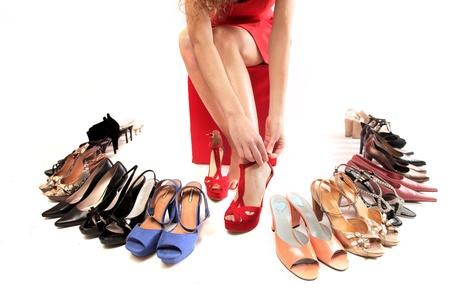 tacones rojos: hermosa mujer elegir zapatos con tacones rojos Foto de archivo