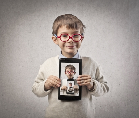 repeated: child shows tablet with portraits of his face repeated Stock Photo