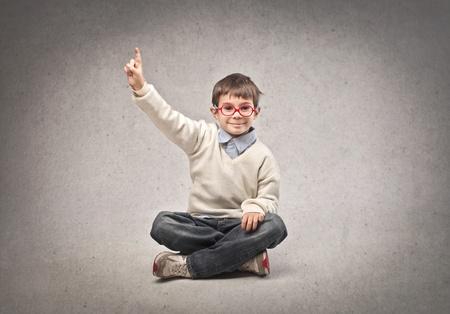 niño pequeño sentado en el suelo, levanta la mano