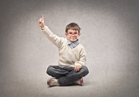 small child sitting on the ground raises his hand