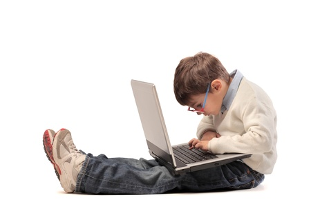 learning computer: small child sitting on the floor with laptop writes Stock Photo
