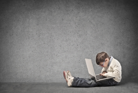 street kid: small child sitting on the floor with laptop writes Stock Photo