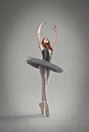 ballerina shoes: beautiful dancer with black tutu posing on gray background Stock Photo