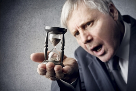 delay: businessman looking with amazement hourglass in his hand Stock Photo