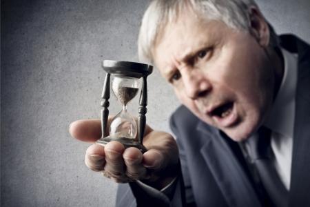 gestion del tiempo: hombre de negocios que mira con asombro reloj de arena en su mano