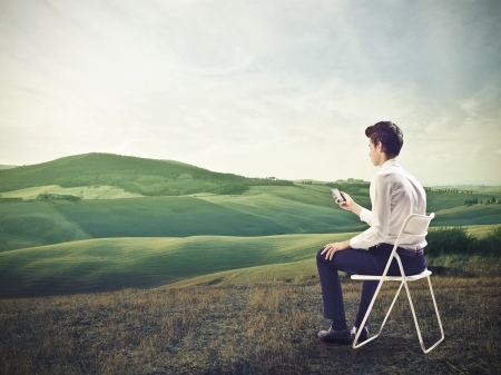 internet profile: young businessman sitting with telephone in hand in beautiful landscape