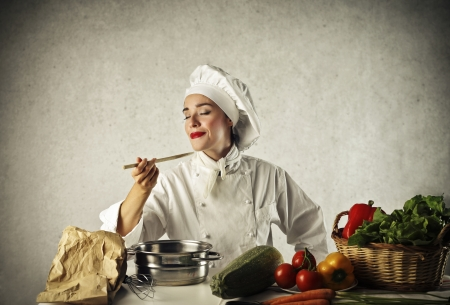 genuine good: young female chef tasting her dishes cooked Stock Photo